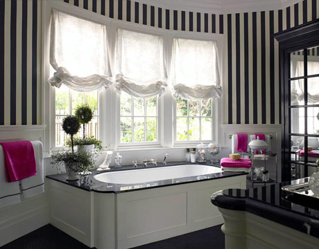 The black and white stripes here make the large bathroom seem cozy. via House Beautiful