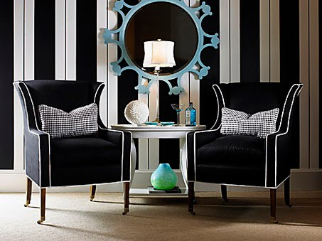 A modern take on a classic wing chair features upholstery in black woven acrylic boldly trimmed in white welting. The slender exposed wood legs have casters. Checkered houndstooth pillows extend the menswear theme and add punch. Here, black and white is dominant against a lively wall of stripes, where a sky-blue mirror stands out like a jewel. This chair from Century Furniture sells for $3,600. Century Furniture