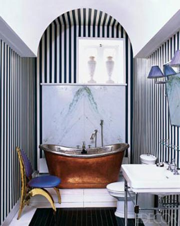 The copper clawfoot bath becomes the focal point in this black and white striped bathroom, via  Elle Decor