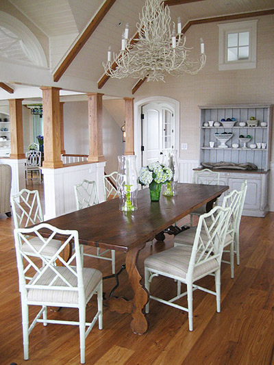All white Chinese Chippendale chairs surround a large old Spanish dining table