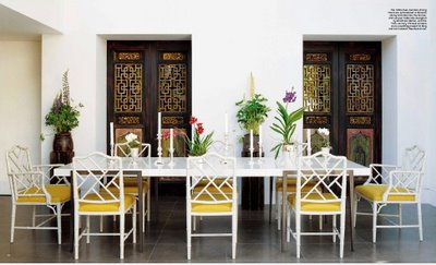 Yellow upholstery paired with white Chinese Chippendale chairs in this dining space add colour and interest to an all white room with strong large, black doors