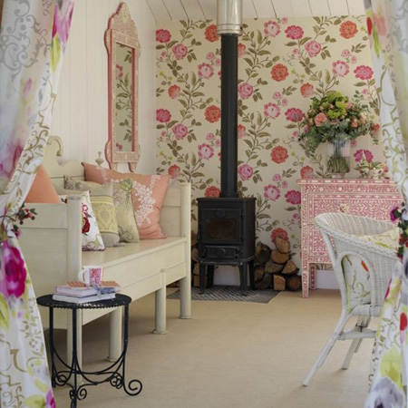 Pink and white floral corner with daybed and strong black pot belly fire stove