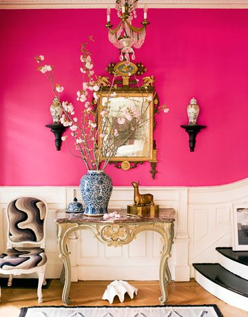 Strong pink hallway with black stairs and gold furnishings, via House Beautiful