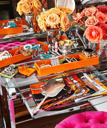 Pink, orange, yellow and red items on a vanity table
