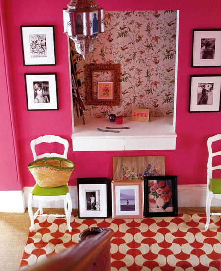 A bold pink hallway with floral wallpaper, and plenty of black and white framed images