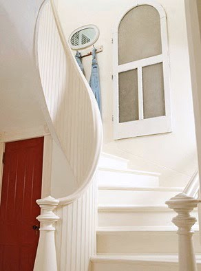 Winding stunning white staircase with red door