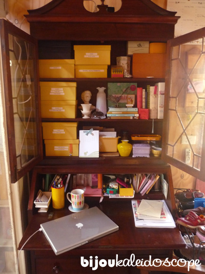 60% of my craft supplies tucked into yellow linen boxes in my secretaire shelves