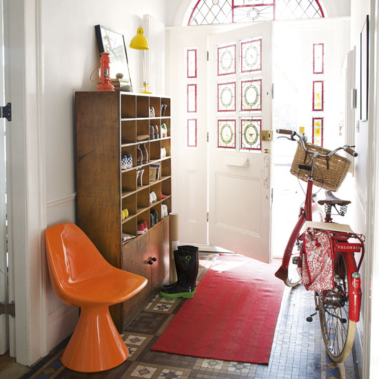 Mid-century shelving used to store shoes in a hallway, via House to Home