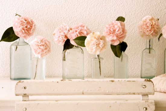 Vintage glass bottles with peach pink roses on mantlepiece