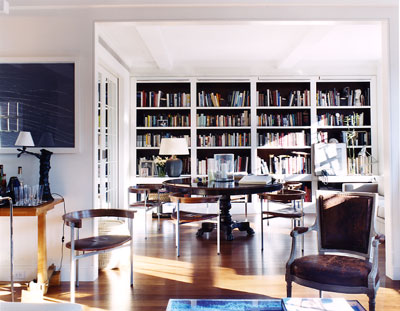 White room, black bookshelves, plenty of books, via David Netto