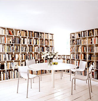 Two walls of books in dining room, via William Waldron