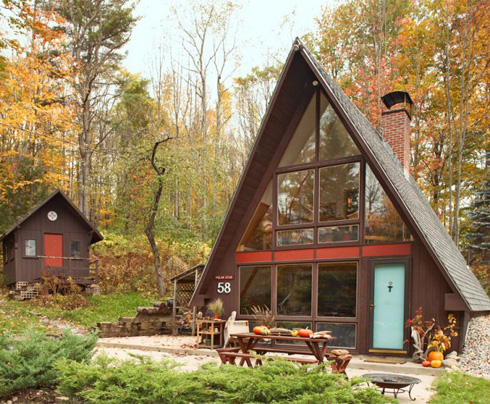 An A-frame house in a woods, via Apartment Therapy