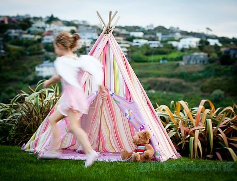 Girl playing with her teepee in a garden