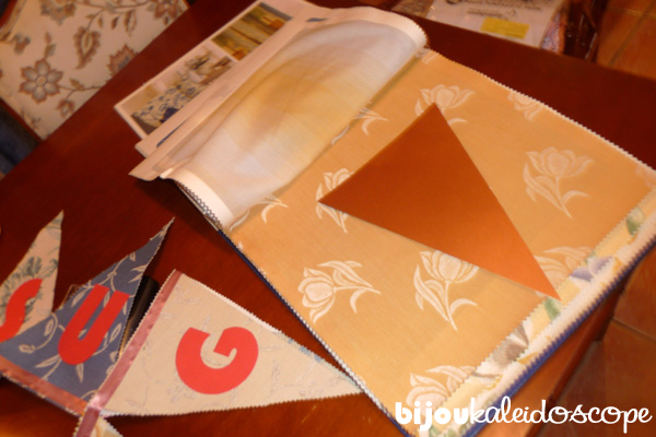 Sizing out the bunting flag template and then cutting out onto upholstery swatches.