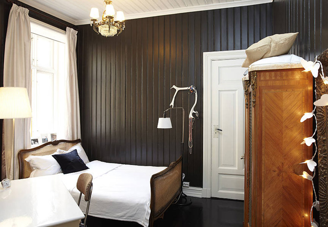 Black cladded bedroom with white bed, white door and brown dresser, via decor abilitate