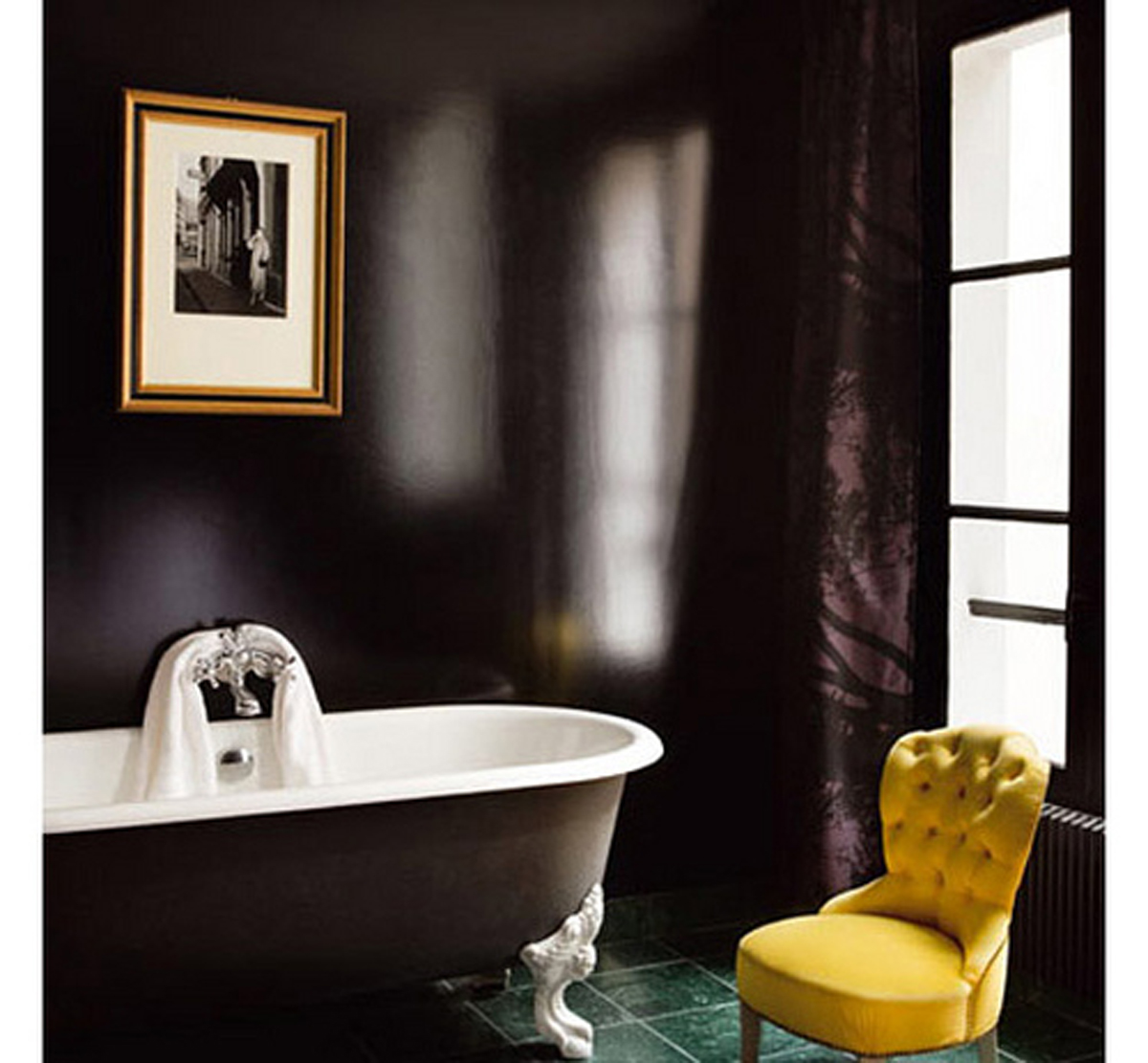 Black glossy bathroom with white tub and yellow chair, via 1 see cubed
