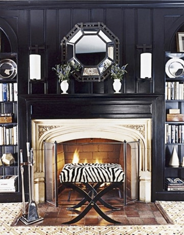 Black living room with warm glow from fireplace, via Meredith Heron Design