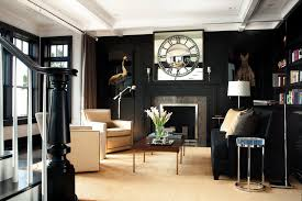 Black living room with bright tall windows and taupe carpet, via dec and you
