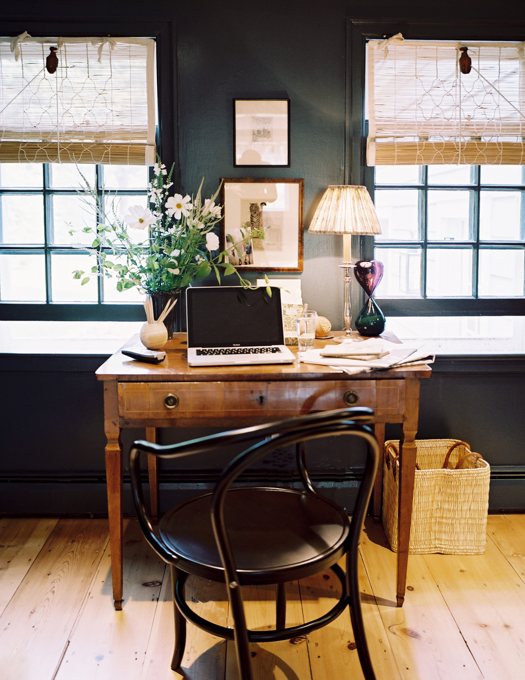 Desk against black wall and windows with light, via Lonny.