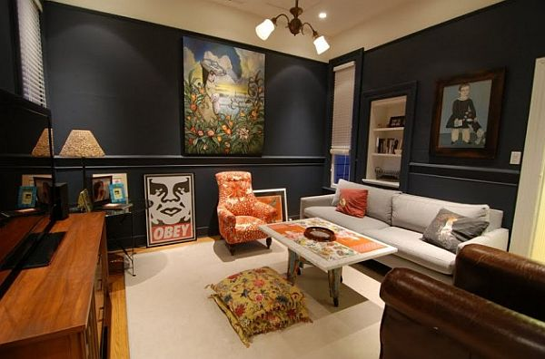 Black living room with orange and cream furnishings, via Decoist