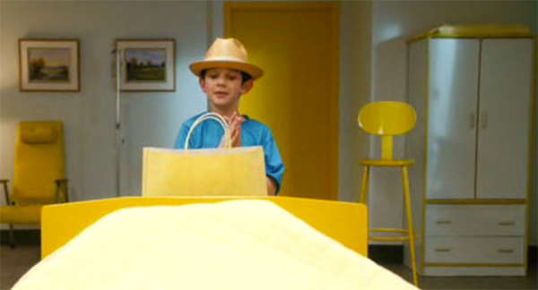 Zach Mills in yellow hat, and yellow and white wardrobe in background with yellow chair, Mr Magorium's Wonder Emporium
