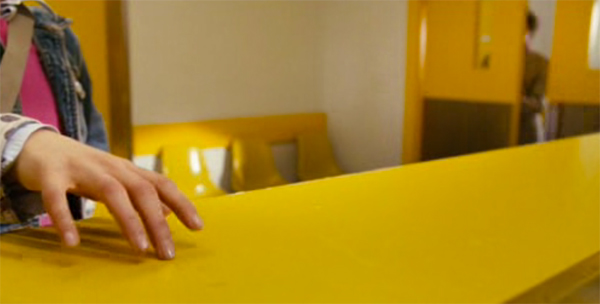 Portman running her fingers on glossy yellow countertop, Mr Magorium's Wonder Emporium