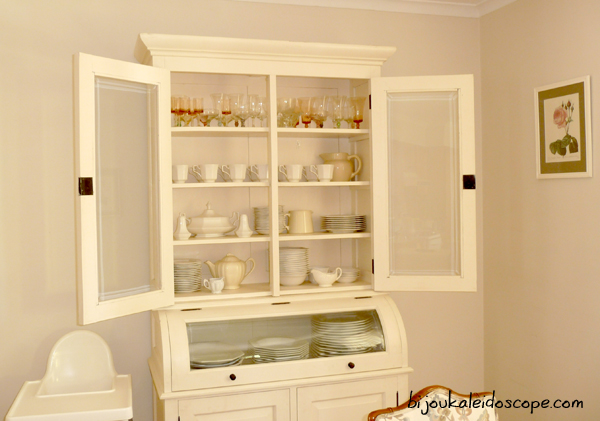 Opened white china cabinet, before