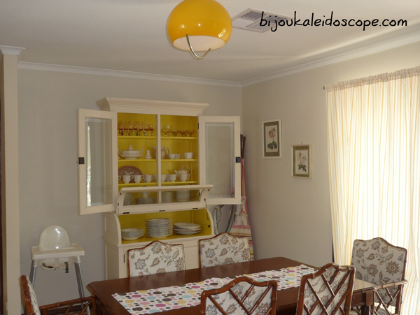 My dining room with the bright yellow light shade and newly painted yellow shelving.