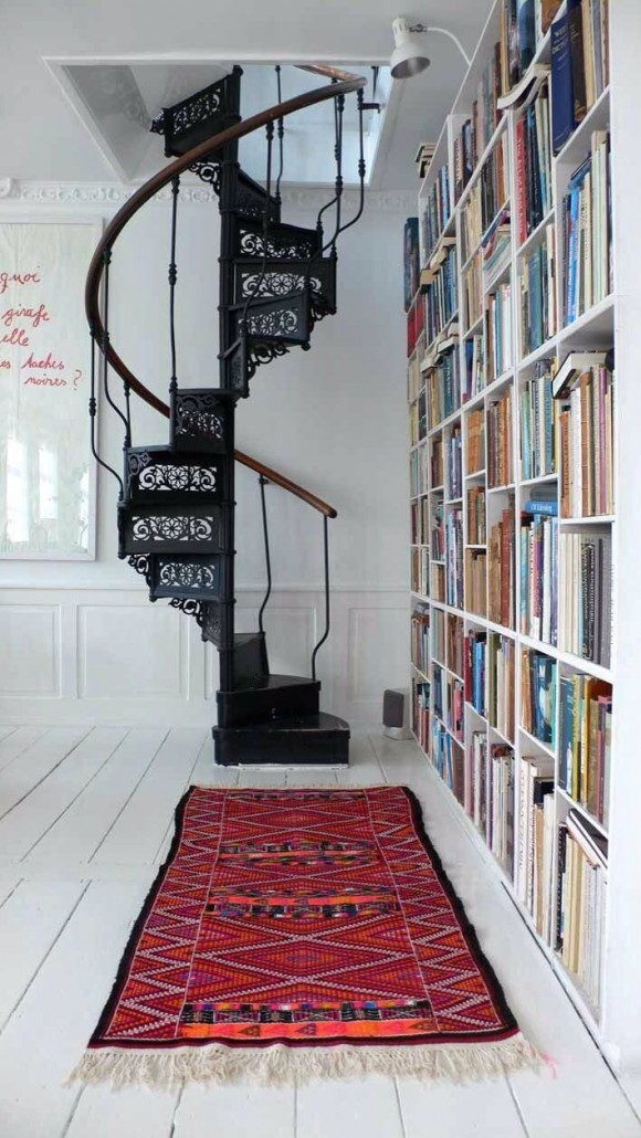 Black spiral staircase in white wooden room with red rug