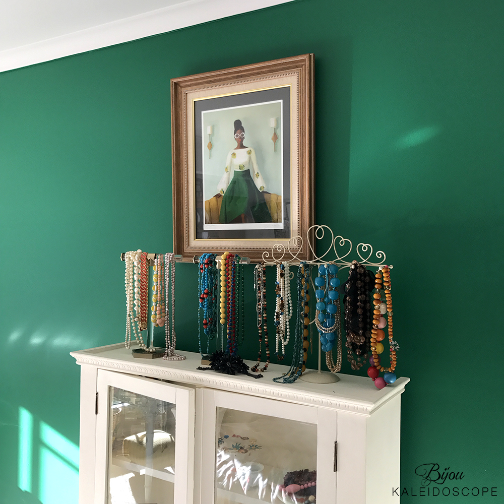 My necklaces on the white cabinet in my bedroom against the green wall