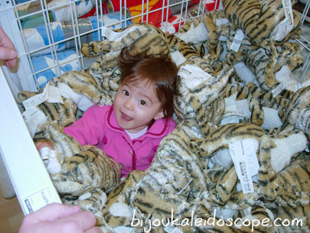 Hannah in the toy tig soft toy basket at IKEA