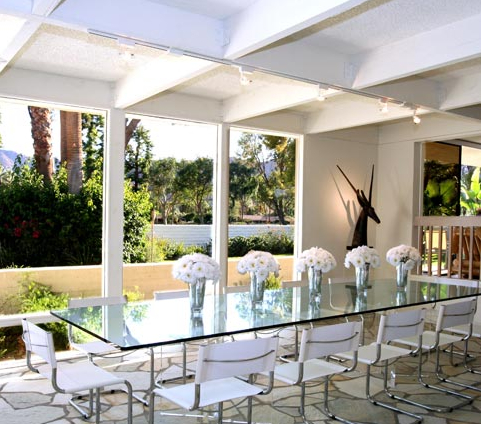 Glass dining table with opaque chairs in a dining space with plenty of floor to ceiling windows