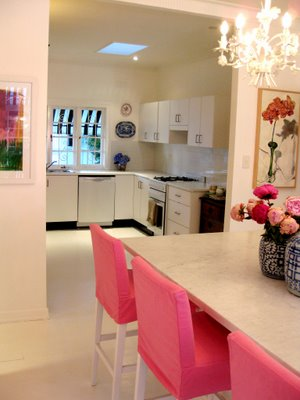 Pink dining chairs in an all white space in Anna Spiro's new Brisbane home