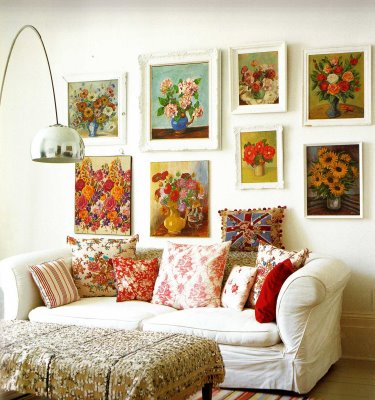 A collection of vintage flower art pieces behind a shabby white lounge