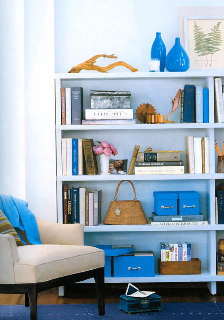 Bookshelf with bright blue accents, via Real Simple: The Organized Home