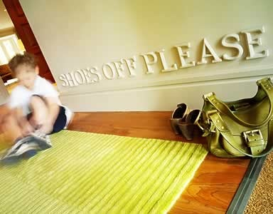 """Stenciled sign """"Shoes off Please"""" on floor on hallway"""