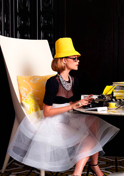 Fancy girl in black and white with yellow hat sitting on giant white chair on vintage typewriter