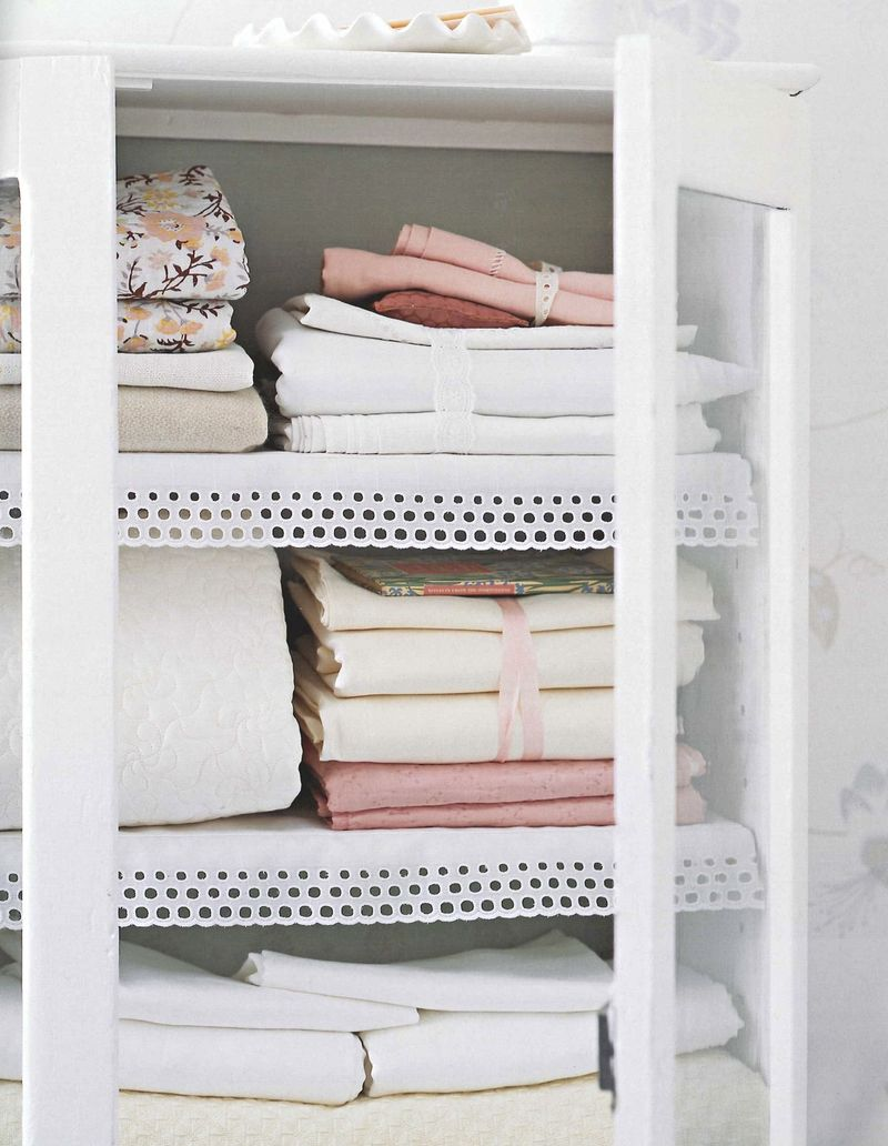 Pretty white armoire with pink and white linens
